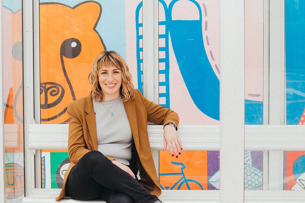 Therapist Rachel Lynch in front of a colorful and bright Easthampton mural. She's wearing a structured brown blazer