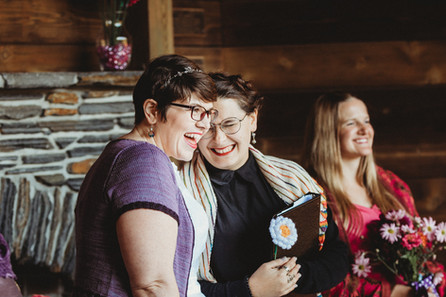 Dani and her officiant smile as Sarah performs a song.