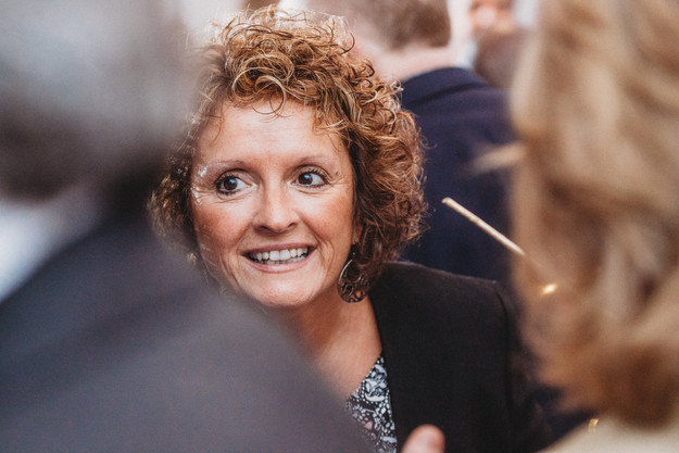 Middle aged woman with curly ginger hair smiles.