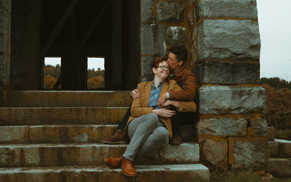 AFAB couple on stone steps suggled up while one kisses the other's forehead.