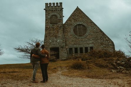Queer couple stands in front of an old rustic building.