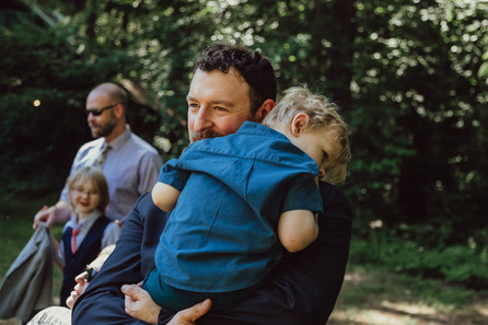 Father holds young child.