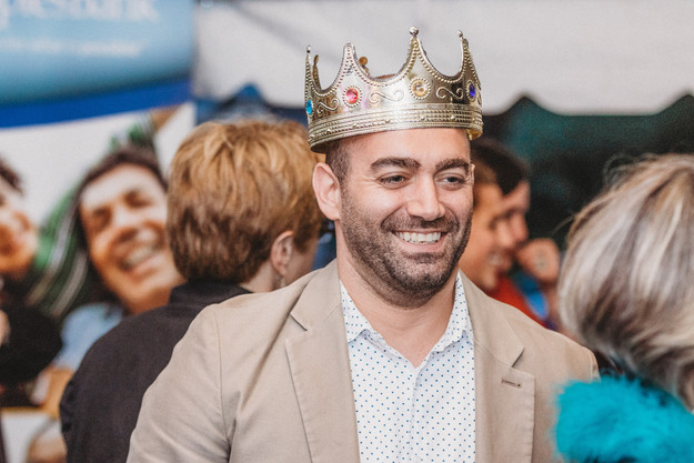 Bearded man wears a plastic gold crown after getting a photo in a photo booth.