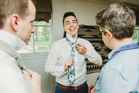 Nonbinary person ties their floral tie before their wedding.