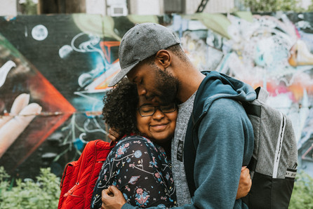 Straight black couple cuddling close together in front of a graffiti mural.
