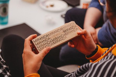 A student holds a block of wood that has sample text laser engraved at various depths.