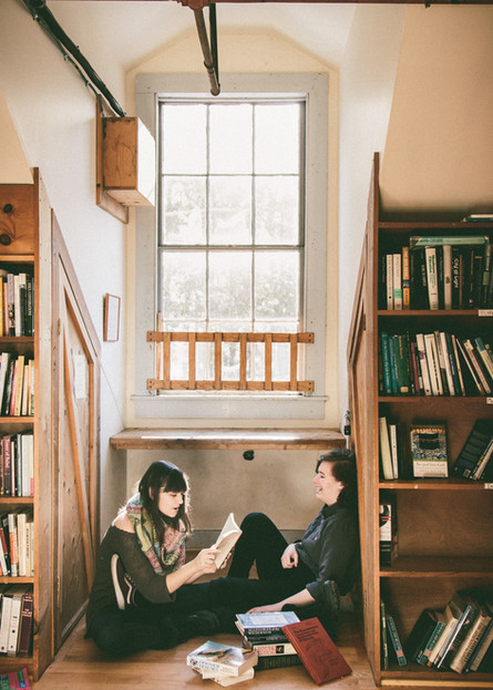 AFAB couple sitting in a small nook in a book store and reading towards each other.