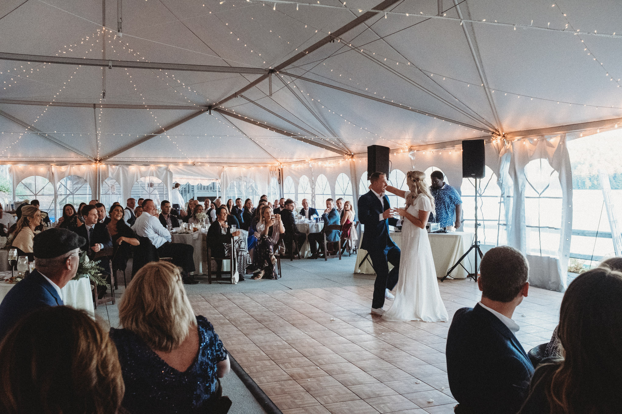 Bride and groom, Jodi Hogan and Eaamon Shaughnesy dance their first dance to country music on  a small dance floor inside of a white event tent.