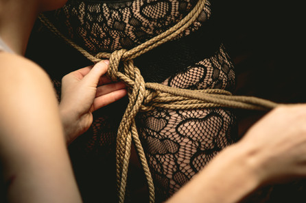 Tieing jute rope over lace clad thighs