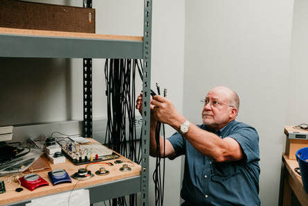 Professor grabbing cables of different lengths.