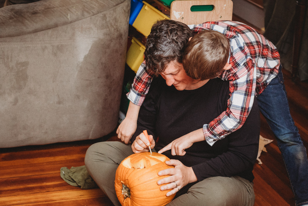 Son drapes over Denise's shoulders as she carves a pumpkin. He points to a part of the pumpkin