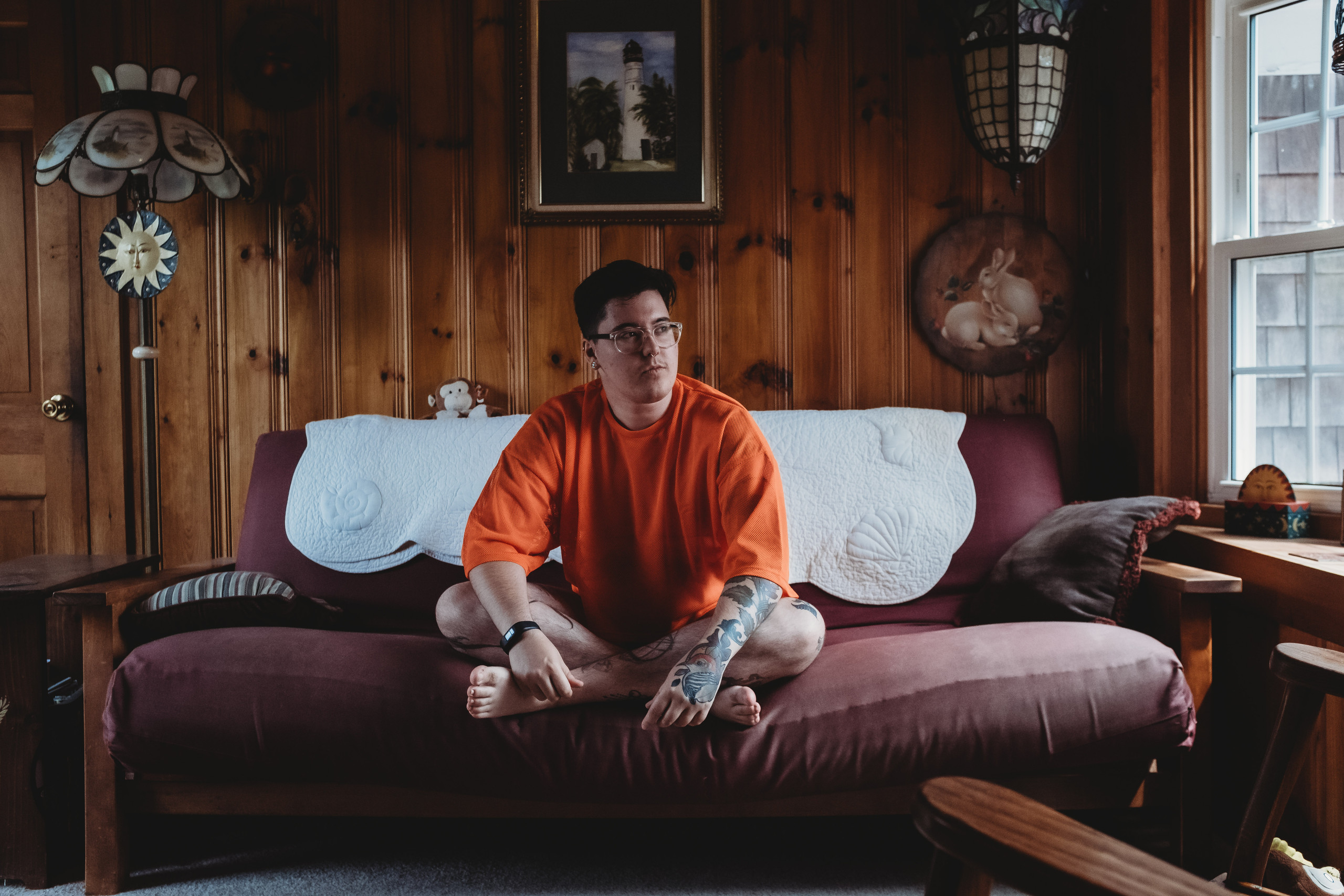 Sage Orville Shea sitting in a neon orange crop top in a vintage 70s room.