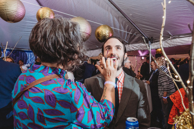 Woman in a bright colorful dress puts purple lipstick on her bearded male friend during a party.