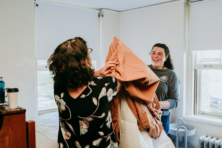 Mother and daughter work to put a cover on a duvet.