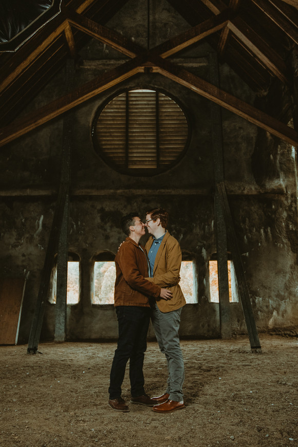 Portrait of a queer couple snuggled at West Boyleston's Old Stone Church.