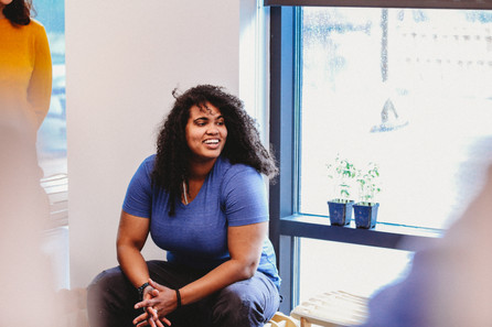 MHC Makerspace Design Mentor Shani Mensing sits by the window as  she listens to her students talk.