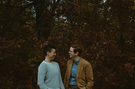B and Emma smiling at each other in front of red leaves and trees.