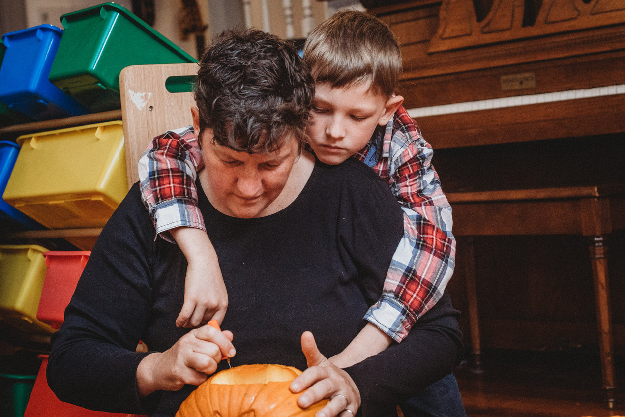 Son drapes over Denise's shoulders as she carves a pumpkin