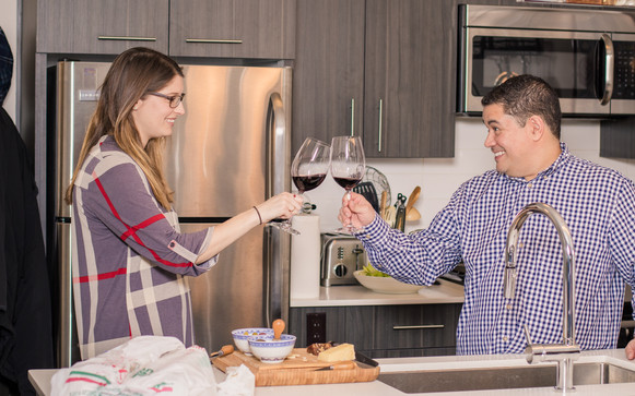 Jimmy and his step daughter Nicole clink wine glasses as a toast before dinner.