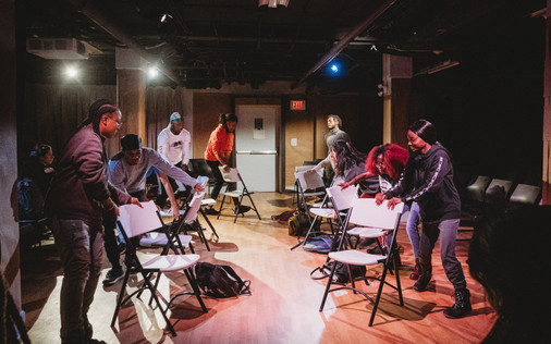 Cast rearranges chairs before breaking into dance
