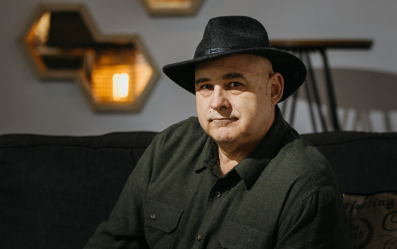 Musician Ken Hebert wearing a black cowboy hat with shadow covering