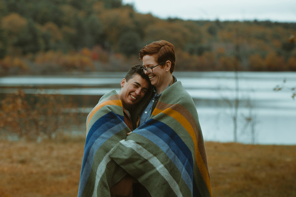LGBT+ couple engagement session, the couple is wrapped in a blanket in front of water.