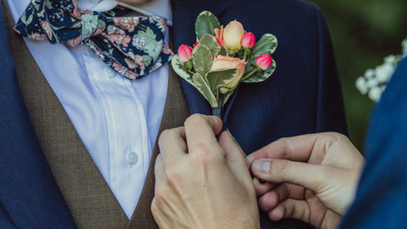 Close up on hands of a queer couple in navy blue suits pin each others floral boutonnieres on each others lapels.