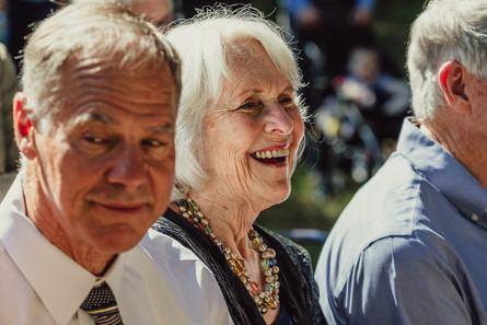Elderly wedding guest smiles.