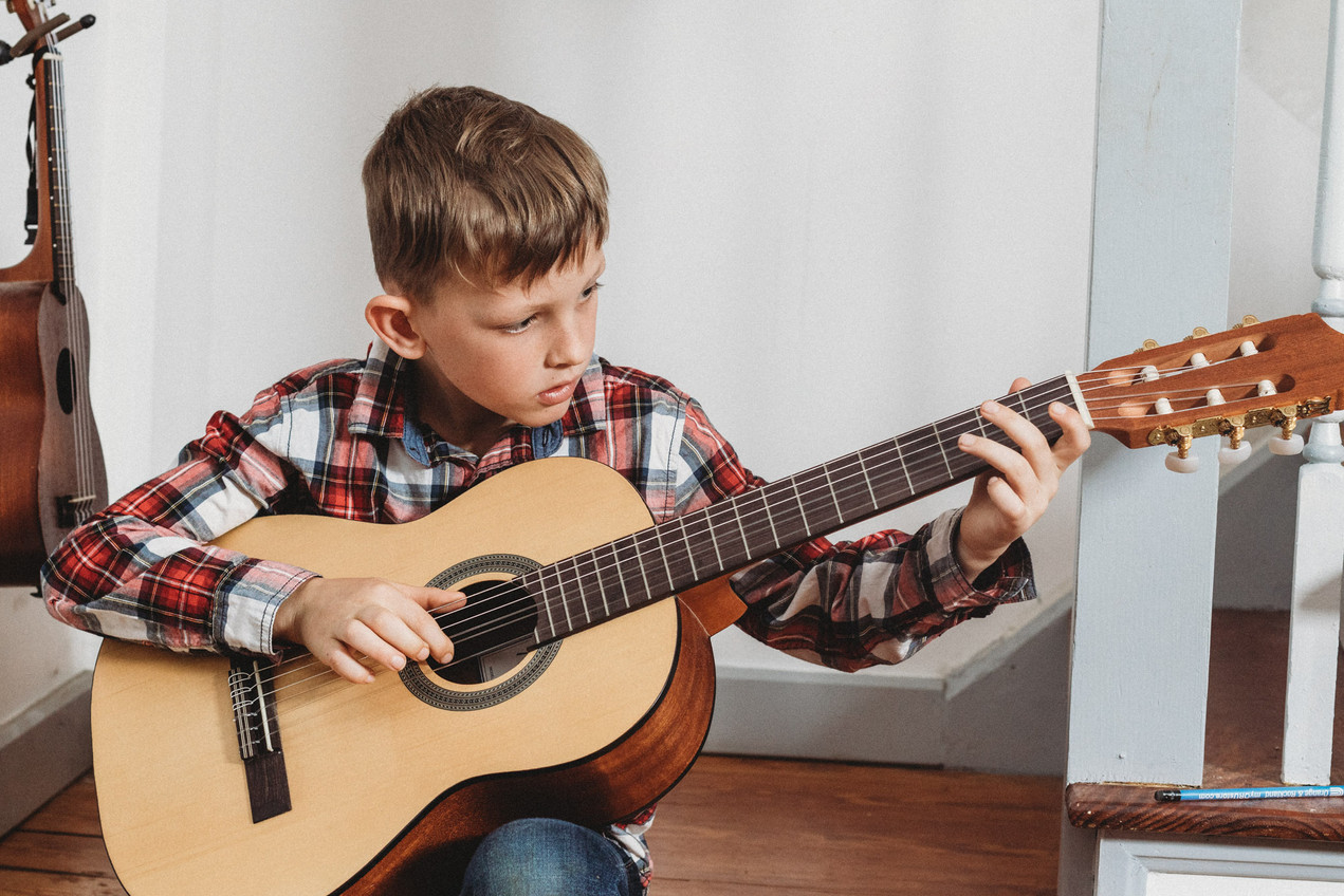 Their son sits at the bottom of their stairs and plays guitar