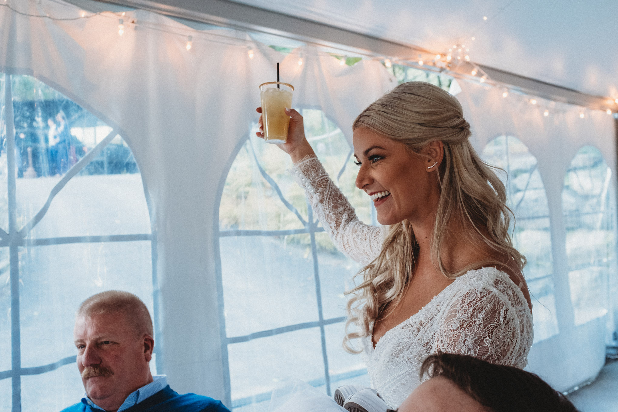 Bride Jodi Hogan comes over to say hi and raises a glass of spiked cider.