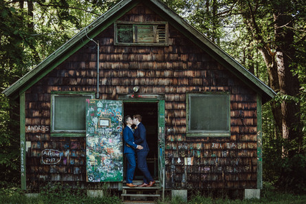 Queer couple kisses in the doorway of an old, wooden, graffitied art cabin.