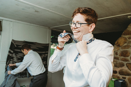 Queer woman ties her bowtie in a small camp building.