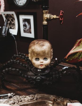 Creepy baby head that's filthy and attached to metal spider legs.