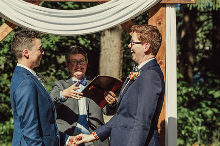 LGBTQIA laughs during ceremony as their officiant makes a joke.