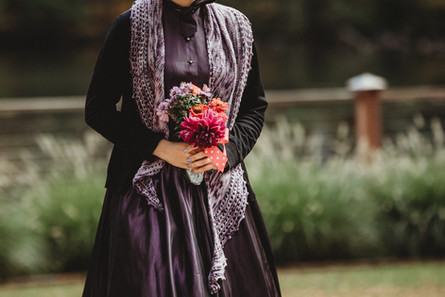 Bridesmade in black and purple carries a boquette arrangement.