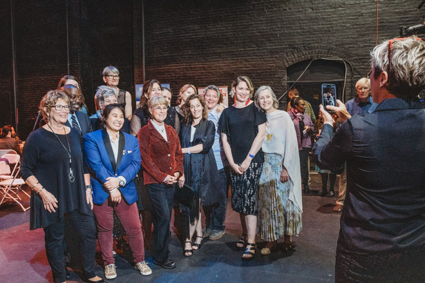 The Chamber of Commerce staff stand together to pose for a group selfie inside the Academy of Music on the back stage.