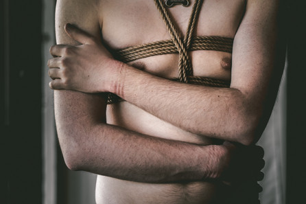 Shirtless man wearing a chest harness in jute, roap marks on his wrists.