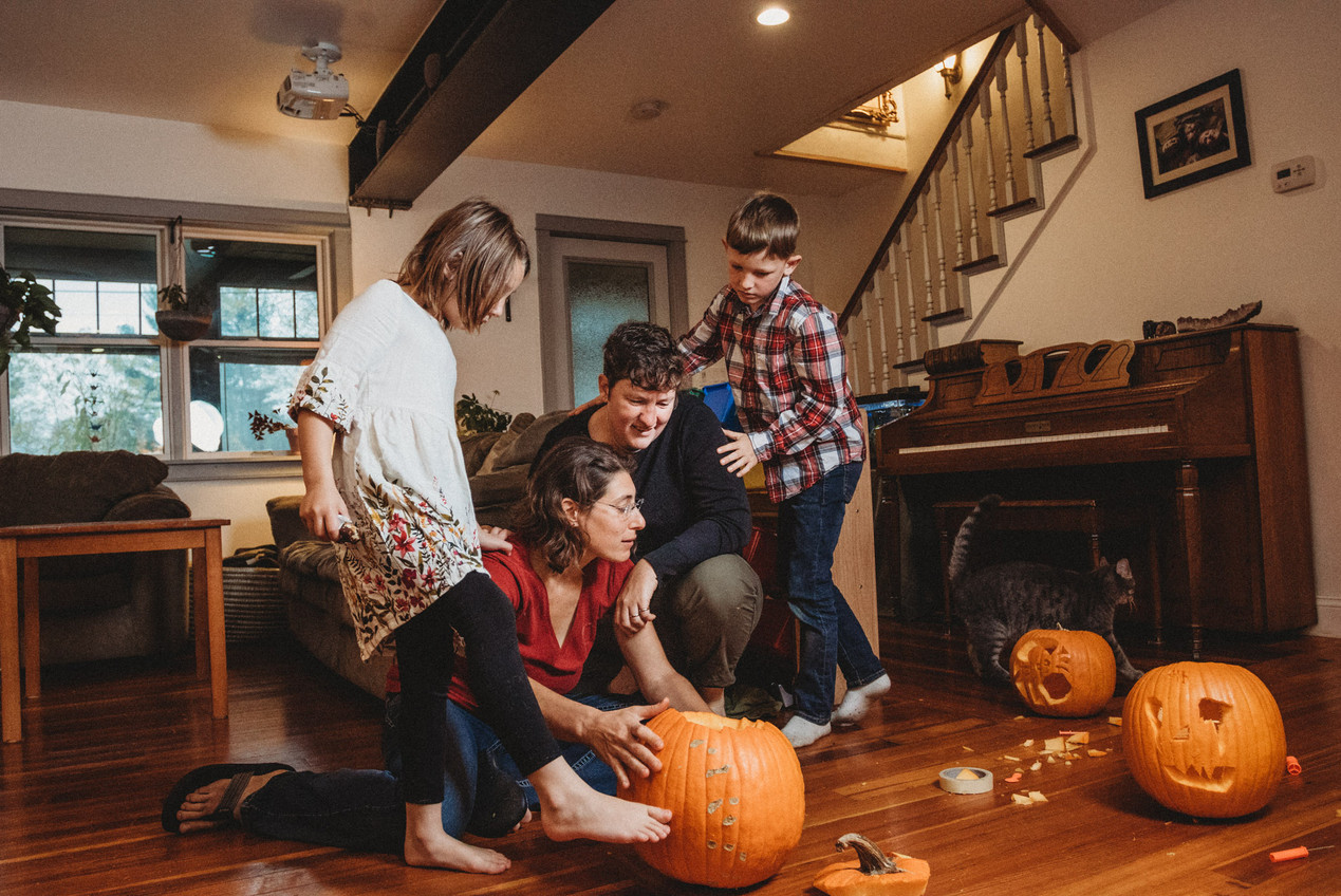 Whole family looks at the pumpkins they've carved.
