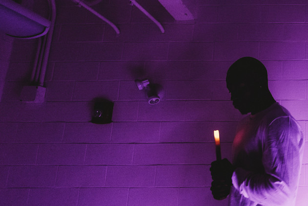 Black man looks down at a lit candle in the closing of a gospel song.