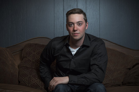 Moodly lit portrait of Austin. He's wearing a black shirt and leaning into frame.