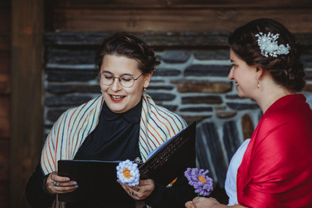 The officiant holds a binder. She's wearing a white knit shawl with rainbow stripes.