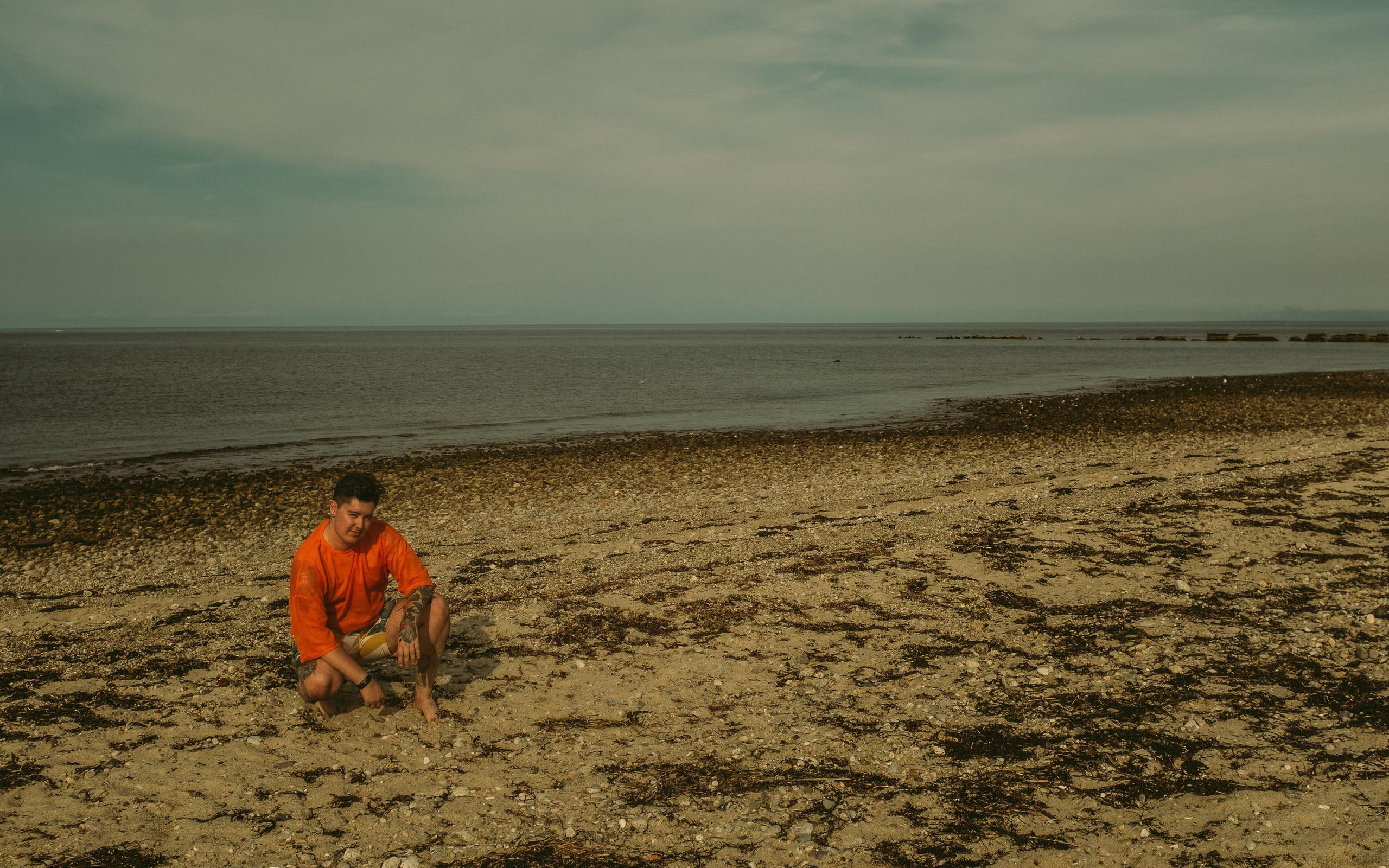 Sage Orville in a neon orange mesh crop top kneeling on the beach.