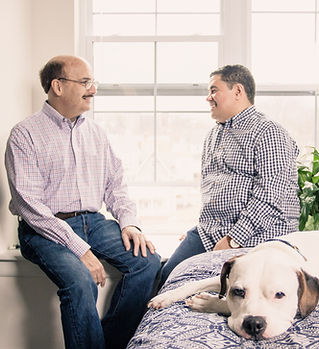 Interacial older gay  male couple  smiling and sitting in front of a window with a pitbull.