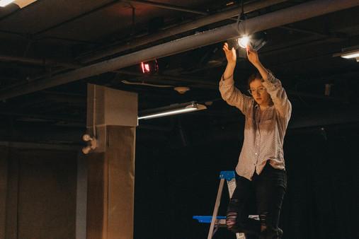 Stage hand adjusts lighting
