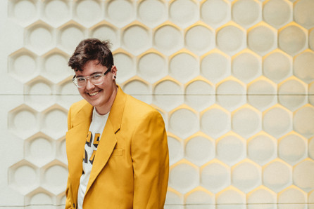 Afab queer masc person in yellow standing in front of a yellow and white honeycomb wall.
