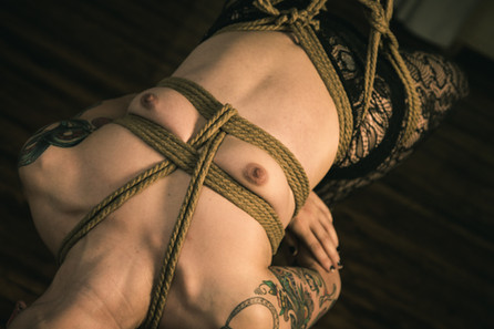 Close up on a woman suspended by her waist in jute rope.