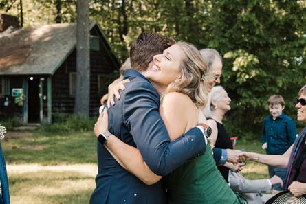 Couple hugs wedding party member.