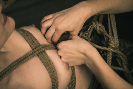The ropes on a jute rope harness are adjusted and repositioned.