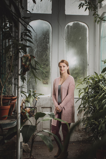 Alyssa staind in the Smith Greenhouse. Tall full body shot surrounded by plants.