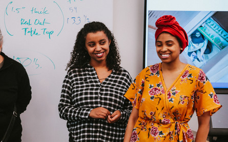 Two students of color stand in front of a large TV and Powerpoint as they talk about the design process for making the desk.